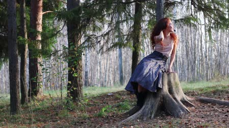sen : Beautiful girl sits on big stump and enjoys in autumn forest