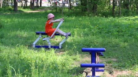 çabaları : Little girl does exercises on outdoor exerciser in green park Stok Video