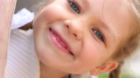 climbed : Pretty little girl peek out from pipe on playground at summer day Stock Footage
