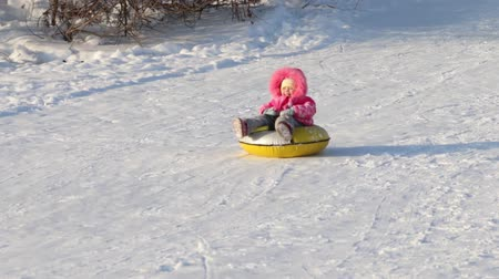 csőrendszer : Little girl slides on a snowtube down from a hill at sunny winter day Stock mozgókép