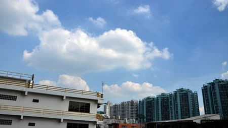 жилье : buildings stand against blue sky and floating clouds, time lapse  Стоковые видеозаписи