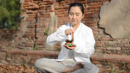 исцелять : Woman playing a tibetan bowl,  traditionally used to aid meditation in Buddhist cultures.