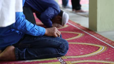 Asian Muslim people offering prayer at a mosque.