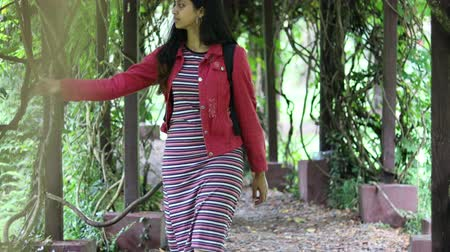 Young millennial girl walking through pergola or shaded with a backpack in a garden 4K video