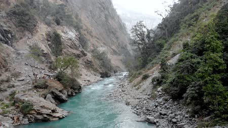 ネパール : River flowing through a gorge and mules with supplies climbing hills in the background