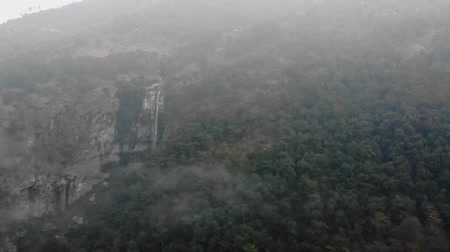 Drone shot of a long waterfall during foggy and dark winter morning