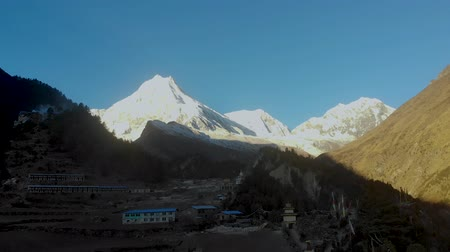 himalája : Rising shot of Mount Manaslu as seen from a remote village in Nepal during Sunrise Stock mozgókép
