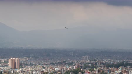 Small domestic airplane on landing at with Kathmandu skyline in the background