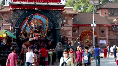 wrzesień : Kathmandu, Nepal - September 11 2019: People walking around Kathmandu Durbar Square during Indra Jatra Festival. Mask and statue of Kaal Bhairav and Swet Bhairav