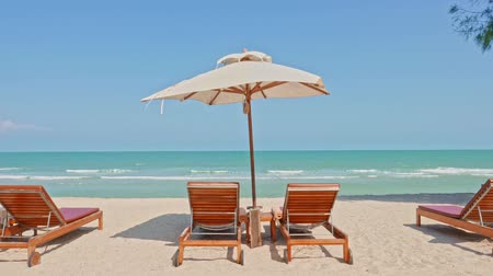 日傘 : Umbrella and chair on the tropical beach and sea with white cloud blue sky for travel 動画素材