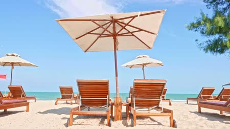 deck chairs : Umbrella and chair on the tropical beach and sea with white cloud blue sky for travel Stock Footage