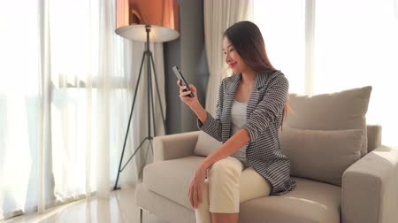 šklebící : Women using mobile phone on sofa