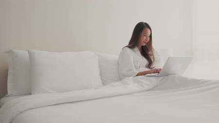 coffee house : Woman using computer laptop on bed in bedroom Stock Footage