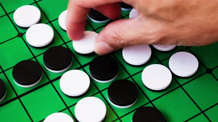 разница : people are playing reversi, board game. this game suitable for adult, kids for practice planning intelligent strategy. its 4k time lapse footage.