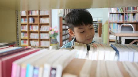 ler : Little Asian cute child reading book in library .