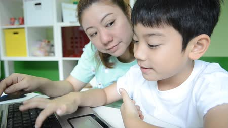 uczenie się : Asian happy Mom is teaching her son Using Laptop in living room