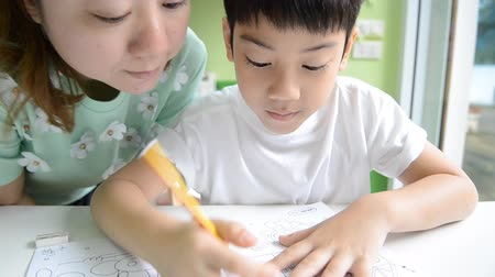 asian family : Asian Mom is helping her son to do homework of the school Stock Footage