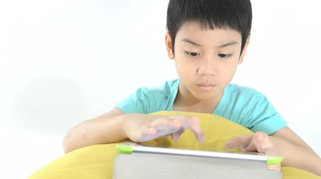 érintőképernyő : Little asian boy smiles with tablet computer acting on his face Stock mozgókép