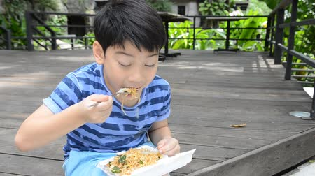 голодный : young asian cute boy  eating  fried chiness noodles.