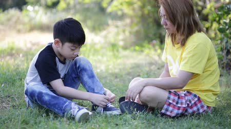 krawat : Asian cute child with mother tying laces at the park .