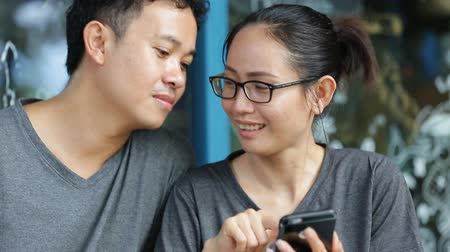 olhares : Happy asian man with girl friend using cell phone together .