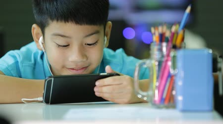 Asian child using a digital tablet with ear buds on his smart phone. Stok Video