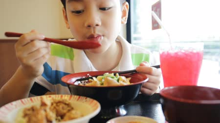 lunch : Happy asian boy eating japanese lunch set ,and looking camera . Stock Footage