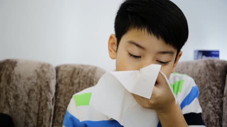 nariz : Little Asian child sick with flu sneezing and clean with tissue paper