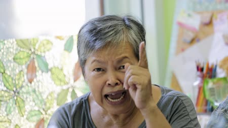 carinho : Angry asian senior woman smiling in front of camera.