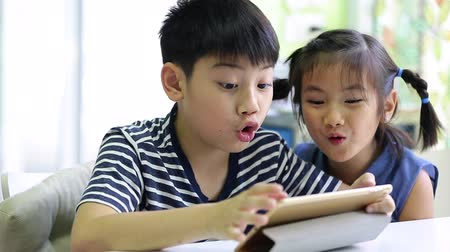 human interest : Little asian boy with tablet computer and little girl playing together Stock Footage