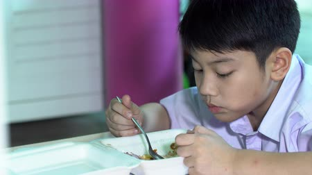 enjoyment : Asian child in student uniform eating food in plastic foam box Stock Footage