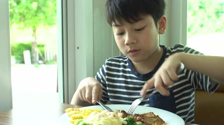 голодный : little Asian boy eating steak with vegetable Salad at restaurant with smile face