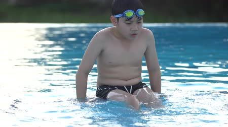 учитель : Asian child playing in the pool ,