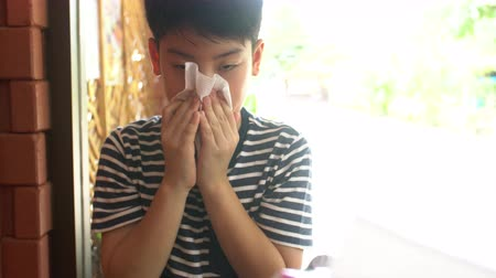 utírat : Little Asian child sick with flu sneezing and clean with tissue paper