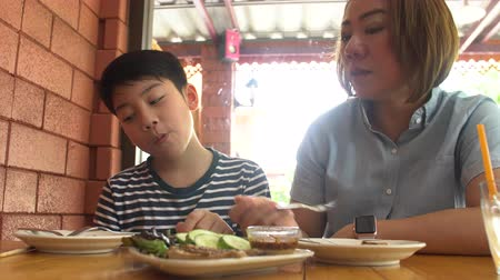 hand feed : Happy Asian mother with her son eating lunch at home,happy asian family enjoy with meal Stock Footage