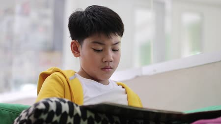 biblioteca : Asian child in student uniform reading and writing to do homework of the school . Stock Footage
