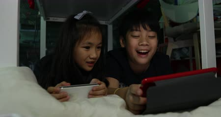elsődleges : Happy asian child playing tablet computer and cell phone together .