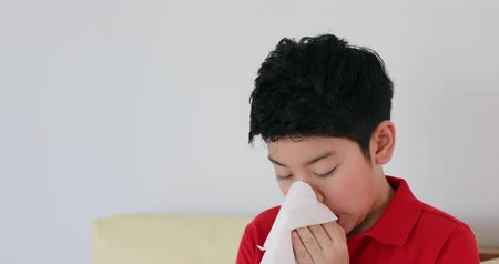tosse : Young Asian boy blows his nose using toilet paper