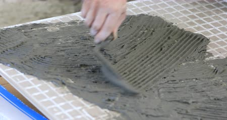 zednická lžíce : Man applies glue to ceramic tile. Professional ceramist is putting mortar on ceramic tile with his special tool