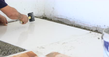 elterjed : Man applies glue to ceramic tile. Professional ceramist is putting mortar on ceramic tile with his special tool