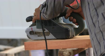 workman : Professional Carpenter grinds Wood In Workshop