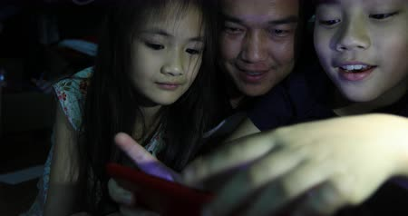 juntos : Asian family,Father daughter and the son watch video from tablet computer .