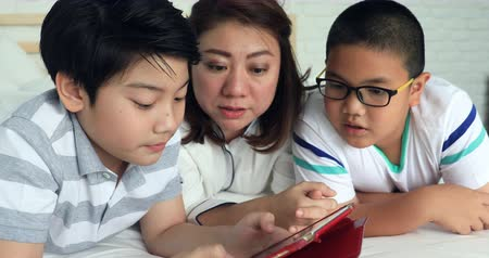 кавказский : Happy asian family mother with her son playing game with tablet computer on the bed at home . Стоковые видеозаписи