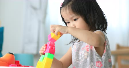 puericultura : Little asian children playing with colorful construction plastic blocks on white Bed at home . Stock Footage