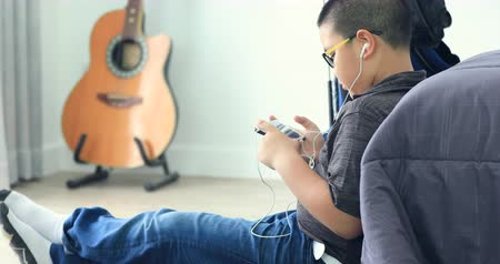 school children : leisure, children, technology and people concept - smiling asian boy with smartphone and headphones listening to music or playing game at home