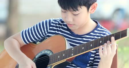 acoustic : Little asian boy is playing the guitar