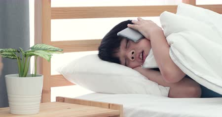 pesadelo : asian boy sleeping and wake up after call in on bed.