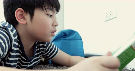 stories : Asian pre teen rest on floor and reading cartoons book .Be smooth face.