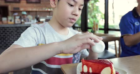 human face : Happy asian boy enjoy eating sweet cake. Stock Footage