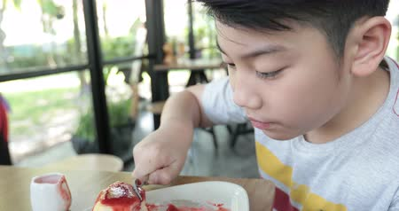 fagylalt : Happy asian boy enjoy eating sweet cake. Stock mozgókép